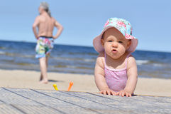 Angry baby. Infant girl on a beach at sea Stock Photos