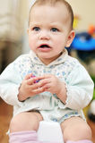 Angry baby on the potty in home Stock Image