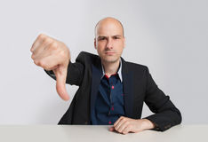 Angry bald businessman showing his thumb down Stock Photo