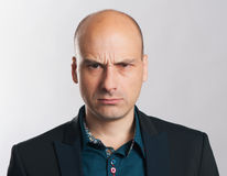 Angry bald dude expressive portrait. Studio shot Stock Images