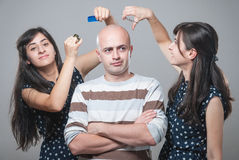 Angry bald guy with two girls. Hair trimming royalty free stock photography