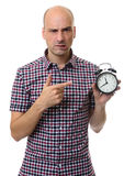 Angry bald man pointing to alarm clock Royalty Free Stock Photo