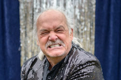 Angry balding man gnashing his teeth. And grimacing in frustration in a head and shoulders portrait in front of silver tinsel on a blue curtain stock image
