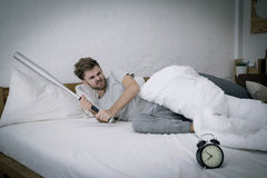 Angry with baseball hit young man screaming at al. Portrait upset angry with baseball hit young man screaming at alarm clock on bedroom. Employee running late Royalty Free Stock Images