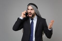 Angry bearded arabian muslim businessman in keffiyeh kafiya ring igal agal classic black suit isolated on gray