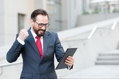 Angry bearded businessman dressed in blue suit threatening with fist to tablet during video conference out of office. royalty free stock photos