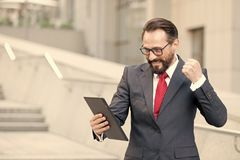 Angry bearded businessman dressed in blue suit threatening with fist to tablet during video conference outdoor office. Businessman royalty free stock photos