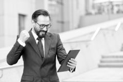 Angry bearded businessman threatening with fist to tablet during video conference outdoor out of office. Businessman happy to read stock images