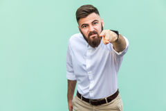 Angry bearded businessman with white shirt looking at camera and pointing finger to you. Royalty Free Stock Images