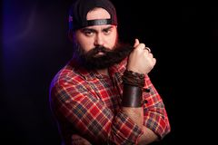 Angry bearded hipster man holding his beard in hands. On black background with red and blue lights behind Stock Photography
