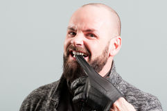Angry bearded male biting his black glove Stock Photos