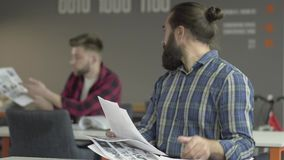 Angry bearded man sitting in the foreground studying papers in the office. Worker turns back to his colleague and throw. Papers to his table, then stands up and stock footage