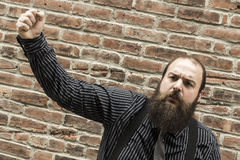 Angry Bearded Man. Well dressed bearded man raises his fist in dismay royalty free stock image