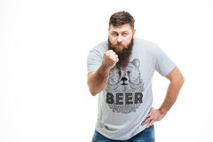 Angry bearded young man standing and showing fist Royalty Free Stock Image