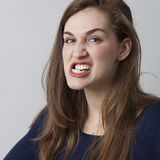 Angry beautiful 20s girl grinding her teeth threatening. Female anger concept - angry beautiful 20s girl grinding her teeth threatening someone,showing royalty free stock photo