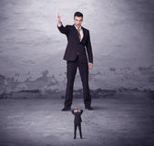 Angry big manager looking at small business man. Concept on background royalty free stock photo