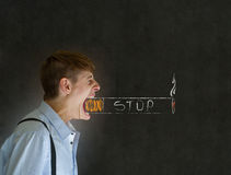 Big mouth man trying to give up smoking cigarette. Angry big mouth businessman, teacher or student man trying to stop smoking chalk cigarette on blackboard Royalty Free Stock Photo