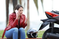 Angry biker calling insurance beside a motorbike. Portrait of an angry biker calling insurance beside a motorbike outdoors in the street Royalty Free Stock Image