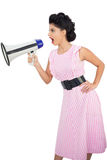 Angry black hair model shouting in a megaphone. On white background Stock Image