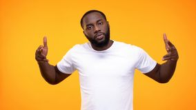 Angry black male pointing finger guns on camera on yellow background, aggression. Stock photo royalty free stock photos