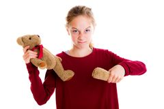 Angry blond girl with broken teddy bear. In front of white background stock photography