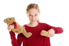 Angry blond girl with broken teddy bear. In front of white background Stock Image