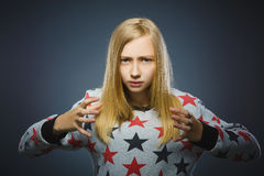 Angry blond girl  on gray background. Negative human emotion, facial expression. Closeup Stock Photo