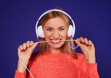 Angry blond in headphones biting cord. On violet Stock Images