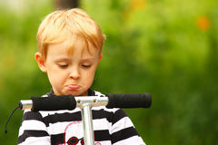 Angry blonde boy. Angry kid on a scooter (green background Stock Photography