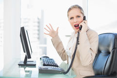 Angry blonde businesswoman screaming on the phone stock images