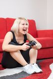 Angry blonde girl playing video games Stock Photo