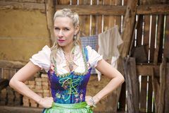 Angry blonde woman in dirndl in front of clothesline. Portrait of angry blonde woman in dirndl in front of clothesline stock photo
