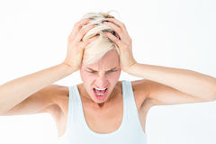 Angry blonde woman screaming and holding her head. On white background Stock Images