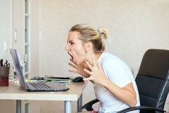 Angry blonde woman working on laptop at home and screaming She`s upset. Freelance, work at home concept stock images