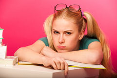Angry, bored schoolgirl with two hair tails and big eyeglasses l Stock Images