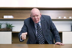 Angry Boss. An angry senior manager slamming his fist on the desk in front of him Stock Images