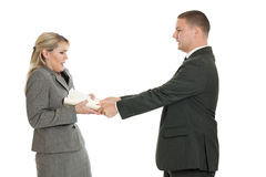 Angry boss. An angry boss shoving a folder at a female employee isolated on white stock image