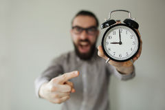 Angry boss with beard holds alarm clock screaming on camera Royalty Free Stock Photo