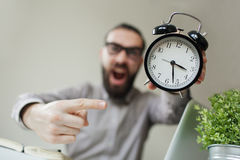 Angry boss with beard holds alarm clock screaming on camera Royalty Free Stock Image