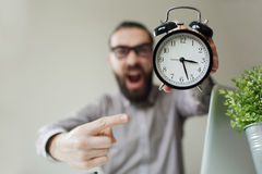 Angry boss with beard holds alarm clock screaming on camera Stock Photos