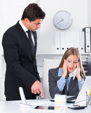 Angry boss blowing up subordinate. Angry boss blowing up female subordinate for being late Royalty Free Stock Photos