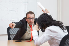 Angry boss firing female colleague by showing the door with his forefinger royalty free stock photography