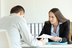 Angry boss giving document to a sad employee stock photos