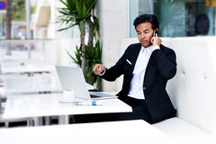 Angry boss having telephone call while work on laptop computer and breakfast in modern coffee shop Stock Image