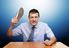 Angry boss knocks shoes on the table. On blue background Stock Photo