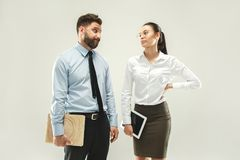 Angry boss. Man and his secretary standing at office or studio. Business men with his colleague. Female and male caucasian models. Office relationships concept Royalty Free Stock Photography