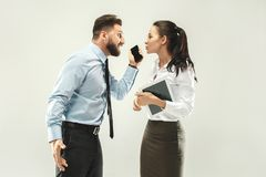 Angry boss. Man and his secretary standing at office or studio. Business men pointing to camera with his colleague. Female and male caucasian models. Office Royalty Free Stock Photography