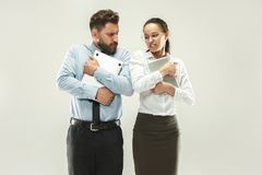 Angry boss. Man and his secretary standing at office or studio. Business men pointing to camera with his colleague. Female and male caucasian models. Office Royalty Free Stock Photos