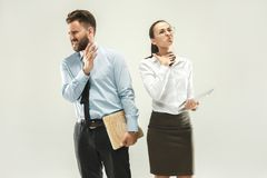 Angry boss. Man and his secretary standing at office or studio. Business men with his colleague. Female and male caucasian models. Office relationships concept Royalty Free Stock Photo