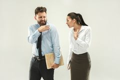 Angry boss. Man and his secretary standing at office or studio. Business man with his colleague. Female and male caucasian models. Office relationships concept Stock Photography